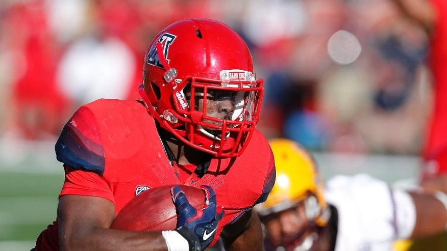 Arizona running back Nick Wilson (28) scores a touchdown during the first half of an NCAA college football game against Arizona State, Friday, Nov. 28, 2014, in Tucson, Ariz. (AP Photo/Rick Scuteri)