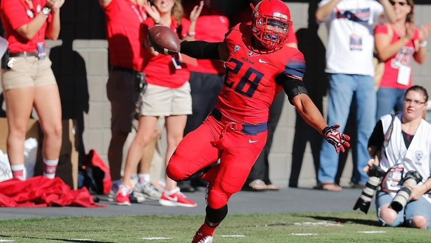 Arizona safety Anthony Lopez (28) celebrates after recovering a fumble for a touchdown during the first half of an NCAA college football game against Arizona State, Friday, Nov. 28, 2014, in Tucson, Ariz. (AP Photo/Rick Scuteri)