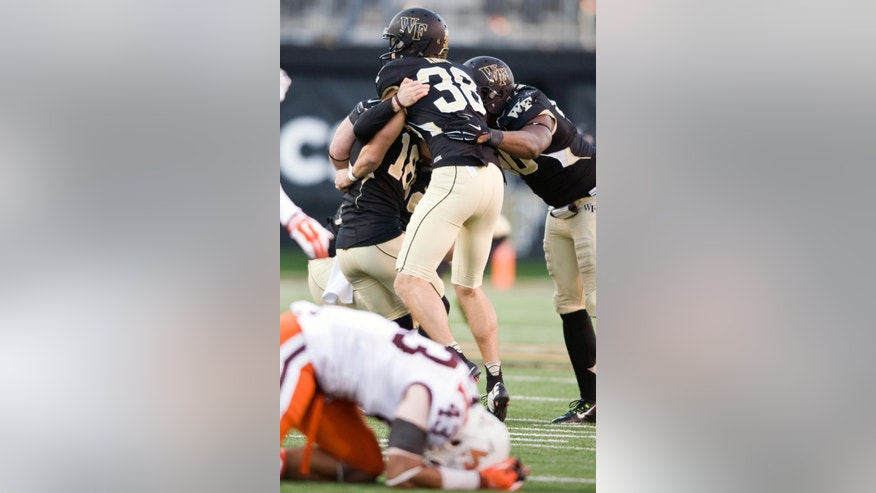 Wake Forest kicker Mike Weaver (18) and Alex Kinal (38) celebrate after Weaver kicked the game-winning field goal in double overtime against Virgina Tech in an NCAA college football game, Saturday, Nov. 22, 2014 at BB&T Field in Winston-Salem, N.C. Wake won 6-3. (AP Photo/Winston-Salem Journal, Andrew Dye)