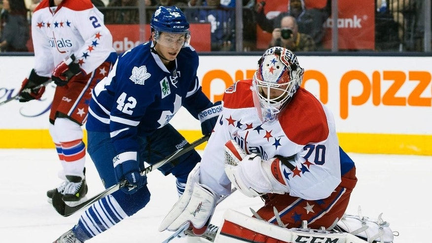Washington Capitals goaltender Braden Holtby, right, makes a save as Toronto Maple Leafs' Tyler Bozak looks for a rebound during the second period of an NHL hockey game, Saturday, Nov. 29, 2014 2014 in Toronto. (AP Photo/Canadian Press, Darren Calabrese)