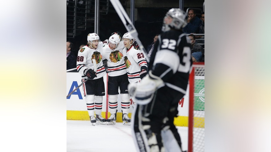 Chicago Blackhawks' Patrick Kane(88), Brad Richards(91) and Kris Versteeg(23) celebrate a goal by Richards as Los Angeles Kings goalie Jonathan Quick, foreground, stands on the ice during the first period of an NHL hockey game Saturday, Nov. 29, 2014, in Los Angeles.(AP Photo/Jae C. Hong)