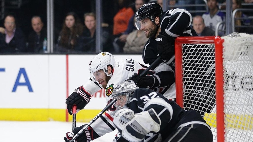 Chicago Blackhawks' Brandon Saad, top left, and Los Angeles Kings' Jarret Stoll compete for the puck next to Kings goalie Jonathan Quick during the first period of an NHL hockey game Saturday, Nov. 29, 2014, in Los Angeles.(AP Photo/Jae C. Hong)