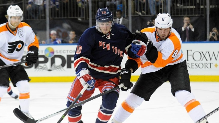 New York Rangers' J.T. Miller, left, and Philadelphia Flyers' Nicklas Grossmann chase after the puck during the second period of an NHL hockey game Saturday, Nov. 29, 2014, at Madison Square Garden in New York. (AP Photo/Bill Kostroun)