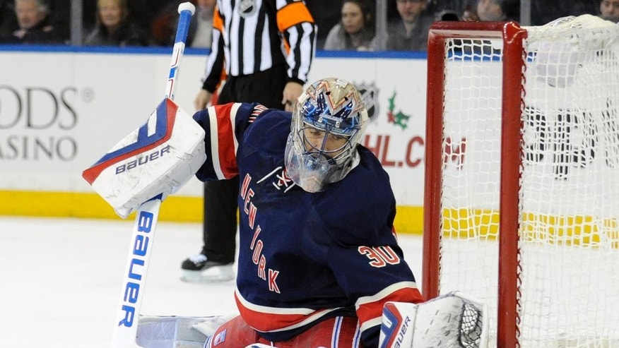 New York Rangers goaltender Henrik Lundqvist, of Sweden, deflects the puck during the first period of an NHL hockey game against the Philadelphia Flyers, Saturday, Nov. 29, 2014, at Madison Square Garden in New York. (AP Photo/Bill Kostroun)