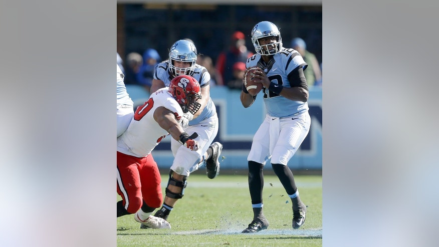 North Carolina quarterback Marquise Williams (12) looks to pass as North Carolina State's Mike Rose rushes during the first half of an NCAA college football game in Chapel Hill, N.C., Saturday, Nov. 29, 2014. (AP Photo/Gerry Broome)