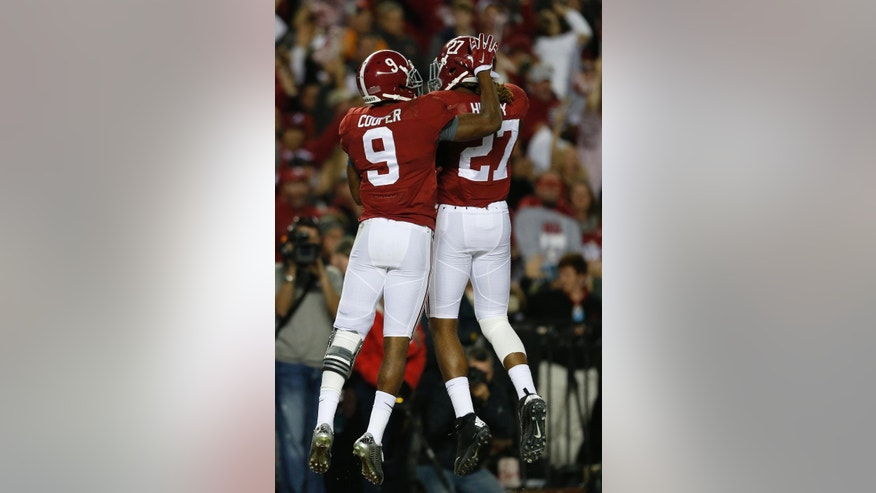 Alabama wide receiver Amari Cooper (9) celebrates his touchdown with Alabama running back Derrick Henry (27) during the second half of the Iron Bowl NCAA college football game against Auburn, Saturday, Nov. 29, 2014, in Tuscaloosa, Ala. (AP Photo/Butch Dill)
