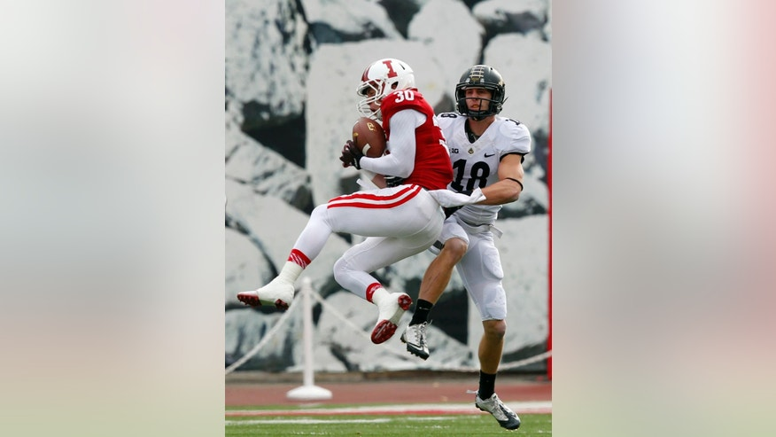 Indiana's Chase Dutra (30) intercepts the ball under pressure from Purdue's Cameron Posey (18) during the first half of an NCAA college football game, in Bloomington, Ind., Saturday, Nov. 29, 2014. (AP Photo/John Sommers II)