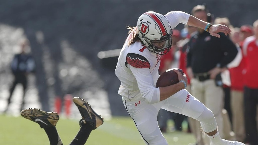 Utah quarterback Travis Wilson, front, is tripped up while running for a first down by Colorado defensive lineman Jimmie Gilbert in the first quarter of an NCAA college football game in Boulder, Colo., on Saturday, Nov. 29, 2014. (AP Photo/David Zalubowski)
