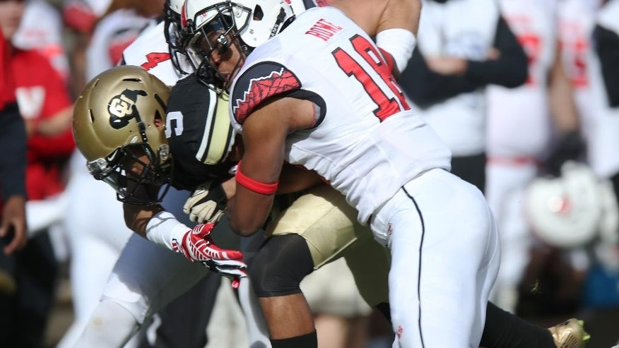 Colorado wide receiver Shay Fields, center, is tackled after catching a pass by Utah defensive backs Eric Rowe, front, and Brian Blechen in the first quarter of an NCAA college football game in Boulder, Colo., on Saturday, Nov. 29, 2014. (AP Photo/David Zalubowski)