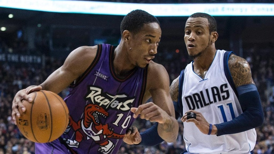 Toronto Raptors' DeMar DeRozan, left, drives at Dallas Mavericks' Monta Ellis during the first half of an NBA basketball game in Toronto on Friday, Nov. 28, 2014. (AP Photo/The Canadian Press, Chris Young)