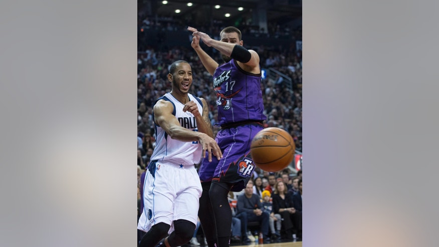 Dallas Mavericks' Devin Harris, left, plays a pass around Toronto Raptors' Jonas Valanciunas during the first half of an NBA basketball game in Toronto on Friday, Nov. 28, 2014. (AP Photo/The Canadian Press, Chris Young)