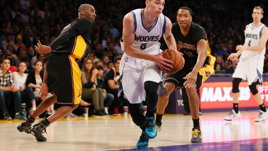 Minnesota Timberwolves' Zach LaVine takes the ball between Los Angeles Lakers' Kobe Bryant, left, and Wesley Johnson, right, during the first half of an NBA basketball game Friday, Nov. 28, 2014, in Los Angeles. (AP Photo/Danny Moloshok)