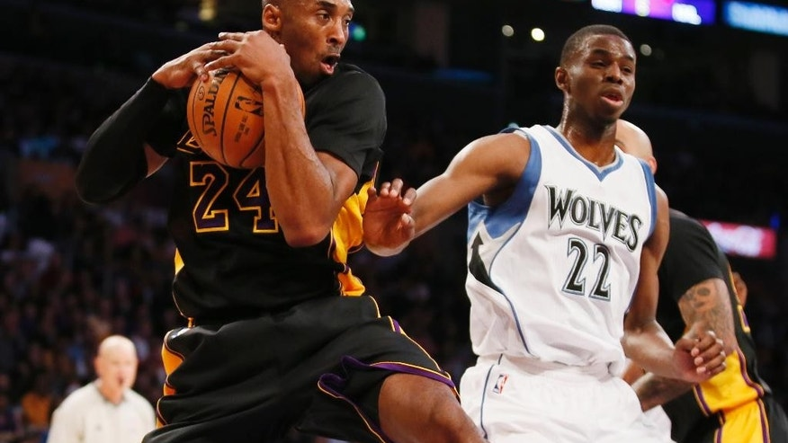 Los Angeles Lakers' Kobe Bryant grabs a rebound in front of Minnesota Timberwolves' Andrew Wiggins during the first half of an NBA basketball game Friday, Nov. 28, 2014, in Los Angeles. (AP Photo/Danny Moloshok)