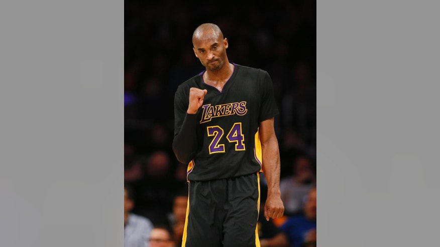 Los Angeles Lakers' Kobe Bryant celebrates after teammate Nick Young scored while being fouled against the Minnesota Timberwolves during the first half of an NBA basketball game Friday, Nov. 28, 2014, in Los Angeles. (AP Photo/Danny Moloshok)
