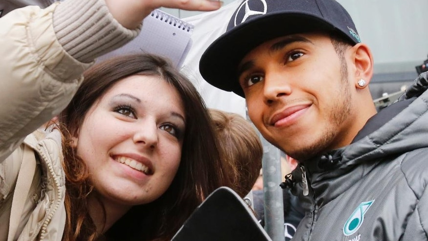 """Britain's F1 Mercedes driver and world champion Lewis Hamilton makes a selfie with fans at the Mercedes """"Stars&Cars"""" event in Stuttgart, Germany, Saturday, Nov. 29, 2014. (AP Photo/Michael Probst)"""