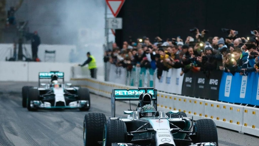 """Germany's F1 driver Nico Rosberg leads Britain's F1 Mercedes driver and world champion Lewis Hamilton at the Mercedes """"Stars&Cars"""" event in Stuttgart, Germany, Saturday, Nov. 29, 2014. (AP Photo/Michael Probst)"""