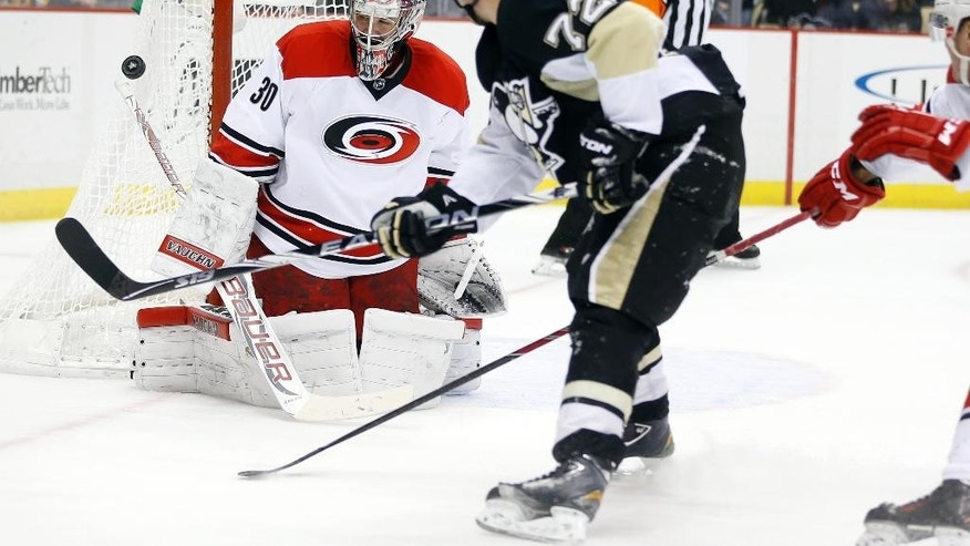 Carolina Hurricanes goalie Cam Ward (30) stops a shot by Pittsburgh Penguins Patric Hornqvist (72) in the second period of an NHL hockey game, Friday, Nov. 28, 2014, in Pittsburgh. (AP Photo/Keith Srakocic)