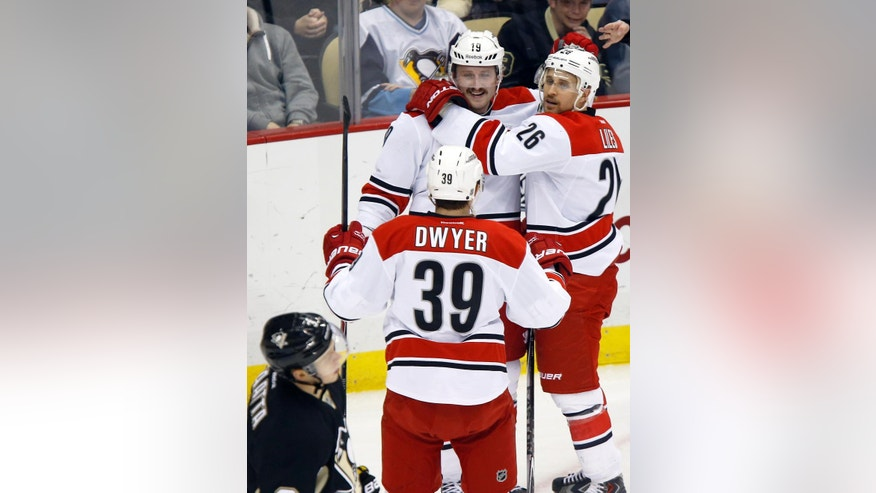 Carolina Hurricanes' Jiri Tlusty (19) is greeted by teammates Patrick Dwyer and John-Michael Liles, right after scoring as Pittsburgh Penguins Olli Maatta skates by in the first period of an NHL hockey game, Friday, Nov. 28, 2014, in Pittsburgh. (AP Photo/Keith Srakocic)