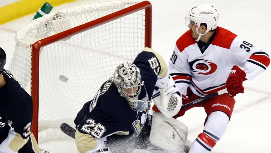 The puck gets past Pittsburgh Penguins goalie Marc-Andre Fleury (29) as Carolina Hurricanes Patrick Dwyer watches the shot from Jiri Tlusty go in during the first period of an NHL hockey game, Friday, Nov. 28, 2014, in Pittsburgh. (AP Photo/Keith Srakocic)