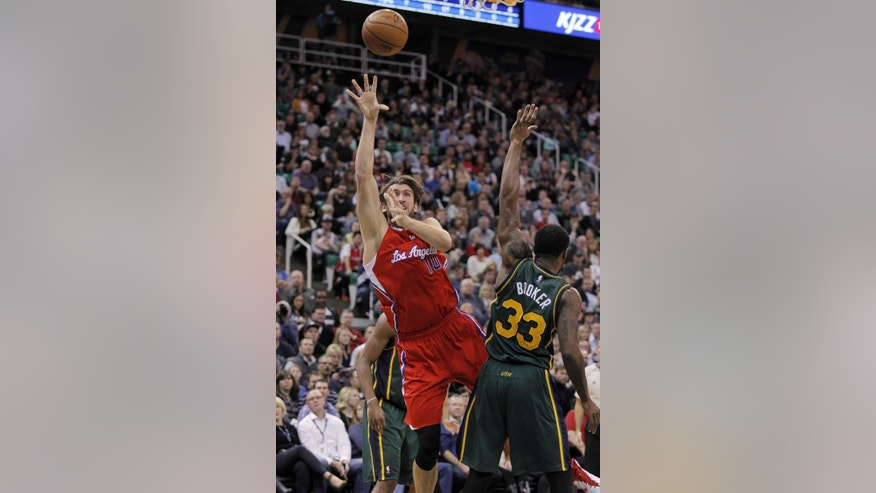 Los Angeles Clippers' forward Spencer Hawes (10) sends a shot to the basket while being tripped up by Utah Jazz's forward Trevor Booker (33) in the first half during an NBA basketball game Saturday, Nov. 29, 2014, in Salt Lake City.  (AP Photo/Steve Wilson)