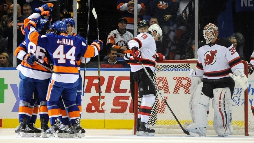 New York Islanders left wing Nikolay Kulemin (86) celebrates his goal with defenseman Calvin de Haan (44) and teammates as New Jersey Devils right wing Martin Havlat (9) and goalie Cory Schneider (35) react in the first period of an NHL hockey game at Nassau Coliseum on Saturday, Nov. 29, 2014, in Uniondale, N.Y. (AP Photo/Kathy Kmonicek)