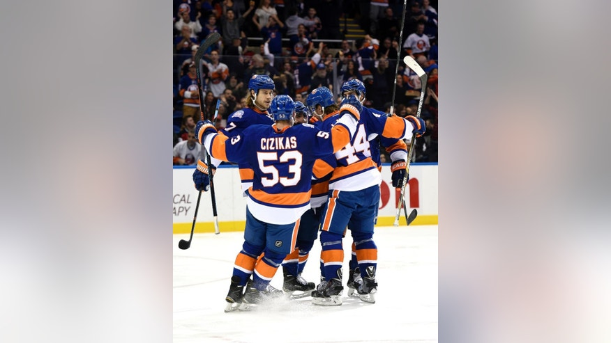 New York Islanders defenseman Cal Clutterbuck celebrates his goal with left wing Matt Martin (17), center Casey Cizikas (53) and teammates in the second period of an NHL hockey game against the New Jersey Devils at Nassau Coliseum on Saturday, Nov. 29, 2014, in Uniondale, N.Y. (AP Photo/Kathy Kmonicek)