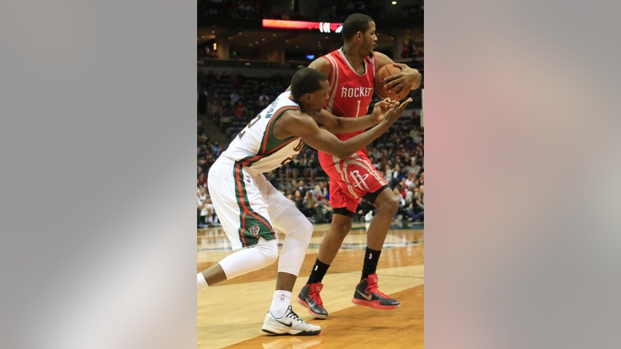 Houston Rockets forward Trevor Ariza, right, steals the ball from Khris Middleton, left, during the second half of an NBA basketball game Saturday, Nov. 29, 2014, in Milwaukee. (AP Photo/Darren Hauck)