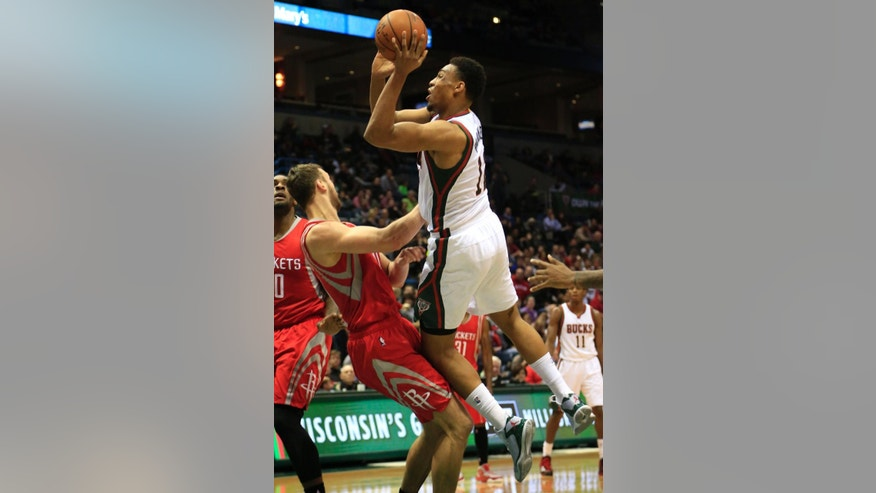 Milwaukee Bucks forward Jabari Parker, right, goes up for a basket against Houston Rockets forward Donatas Motiejunas, left, during the second half of an NBA basketball game Saturday, Nov. 29, 2014, in Milwaukee. (AP Photo/Darren Hauck)