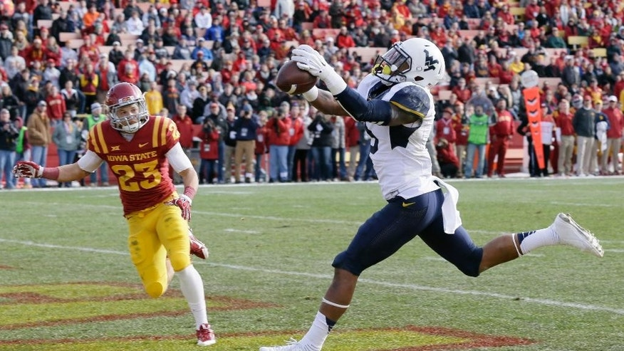 West Virginia wide receiver Mario Alford catches a 29-yard touchdown pass in front of Iowa State defensive back Darian Cotton, left, during the first half of an NCAA college football game, Saturday, Nov. 29, 2014, in Ames, Iowa. (AP Photo/Charlie Neibergall)