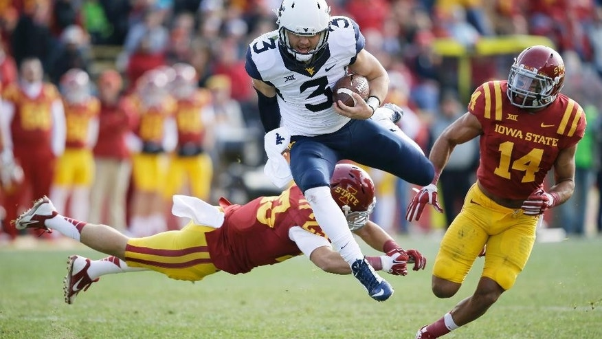 West Virginia quarterback Skyler Howard (3) runs from Iowa State defenders Darian Cotton, left, and Jared Brackens (14) during the first half of an NCAA college football game, Saturday, Nov. 29, 2014, in Ames, Iowa. (AP Photo/Charlie Neibergall)