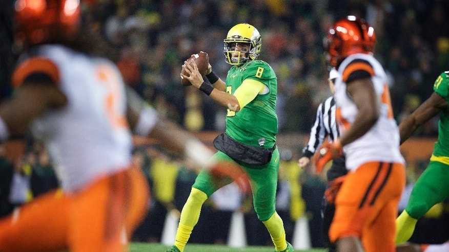 Oregon quarterback Marcus Mariota (8) throws a pass during the first quarter of an NCAA college football game against Oregon State in Corvallis, Or., Saturday, Nov. 29, 2014. (AP Photo/Troy Wayrynen)