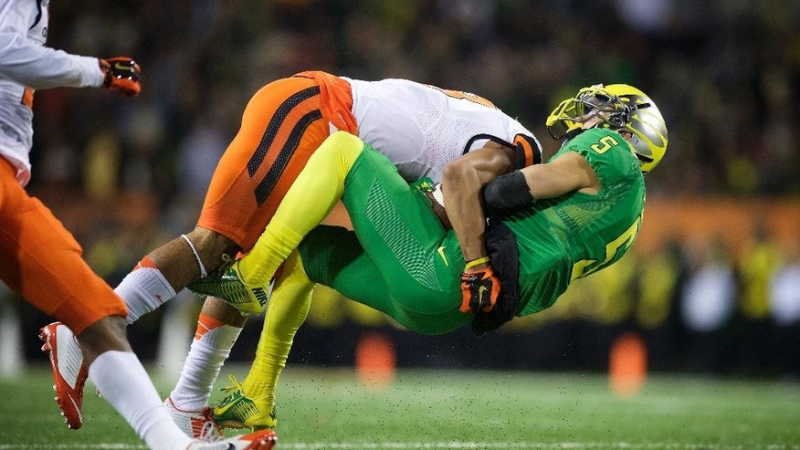 Oregon State defender Tyrequek Zimmerman (8) tackles Oregon's Devon Allen (5) during the first quarter of an NCAA college football game in Corvallis, Or., Saturday, Nov. 29, 2014. (AP Photo/Troy Wayrynen)