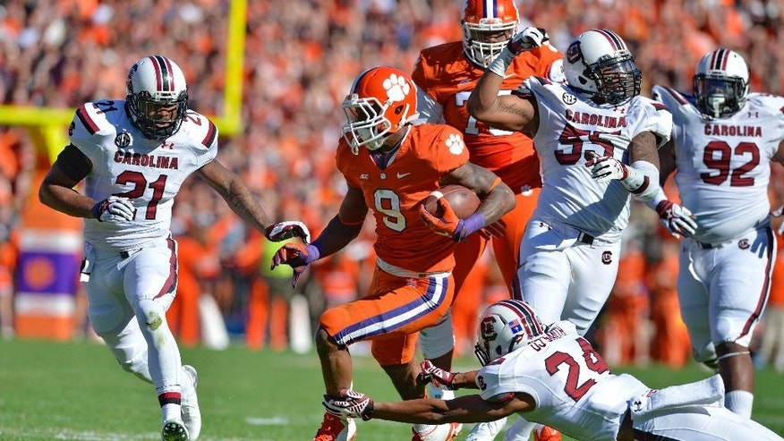 Clemson running back Wayne Gallman avoids the tackle attempt of South Carolina's D.J, Smith during the first half of an NCAA college football game against  in Clemson, S.C., Saturday, Nov. 29, 2014. (AP Photo/Richard Shiro)