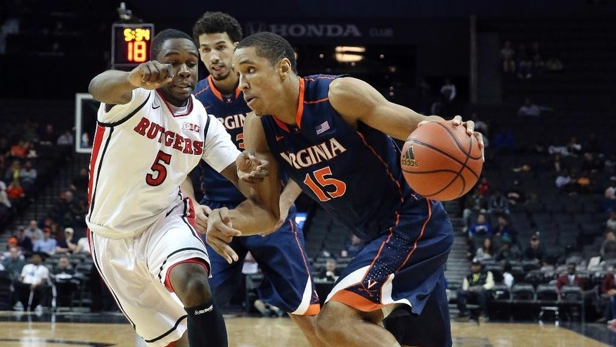 Virginia guard Malcolm Brogdon (15) drives around Rutgers guard Mike Williams (5) in the first half of an NCAA college basketball game, the championship game of the Barclays Center Classic, Saturday, Nov. 29, 2014, in New York. (AP Photo/John Minchillo)