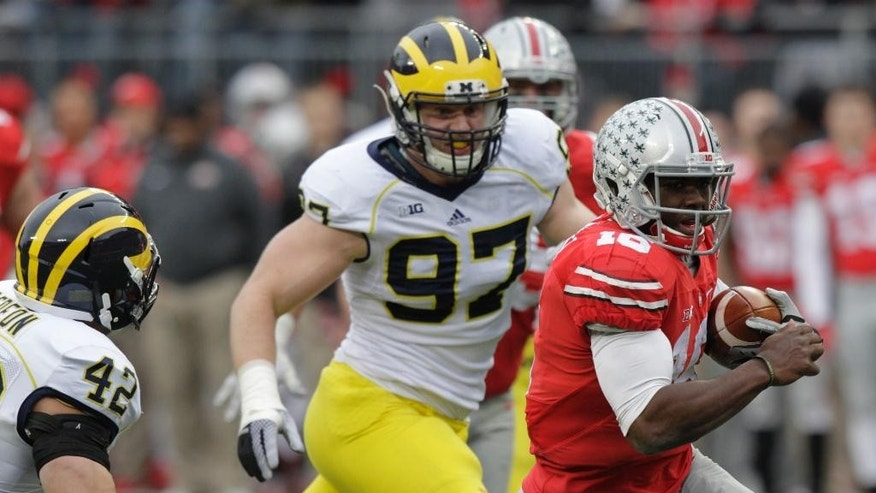 Ohio State J.T. Barrett, right, outruns Michigan defenders Ben Gedeon, left, and Brennen Beyer to score a touchdown during the second quarter of an NCAA college football game Saturday, Nov. 29, 2014, in Columbus, Ohio. (AP Photo/Jay LaPrete)