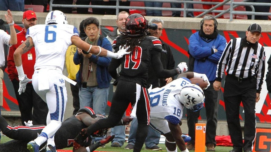 Field Judge Bobby Ables, right, looks on as Kentucky's Stanley Williams crosses the goal line during the first half of an NCAA college football game Saturday, Nov. 29, 2014, in Louisville, Ky. From left is Kentucky's Blake Bone, and Louisville's Terell Floyd. (AP Photo/Garry Jones)