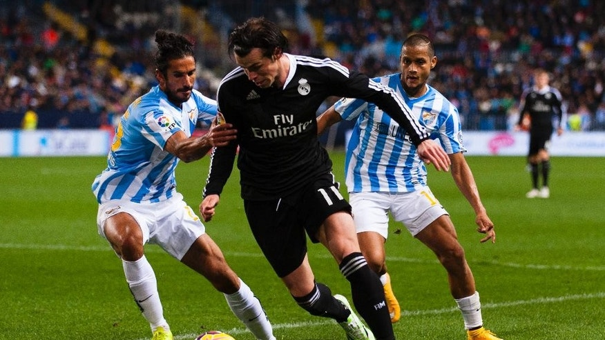 Real Madrid's Gareth Bale from Wales, center, duels for the ball against Marcos Alberto Angeleri from Argentina, left, and Roberto Jose Rosales from Venezuela, right, during a Spanish La Liga soccer match between Malaga and Real Madrid at La Rosaleda stadium in Malaga, Spain, Saturday Nov. 29, 2014. (AP Photo/Daniel Tejedor)