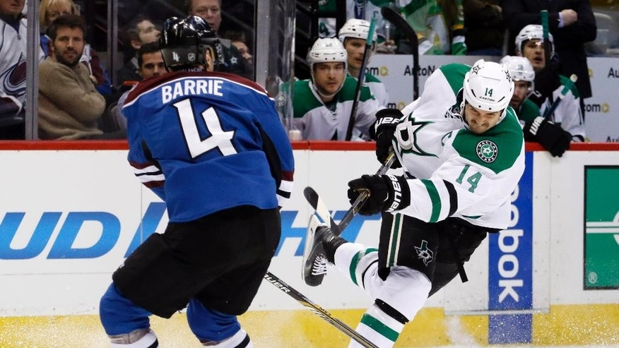 Dallas Stars left wing Jamie Benn (14) shoots past Colorado Avalanche defenseman Tyson Barrie (4) during the second period of an NHL hockey game Saturday, Nov. 29, 2014, in Denver. (AP Photo/Jack Dempsey)