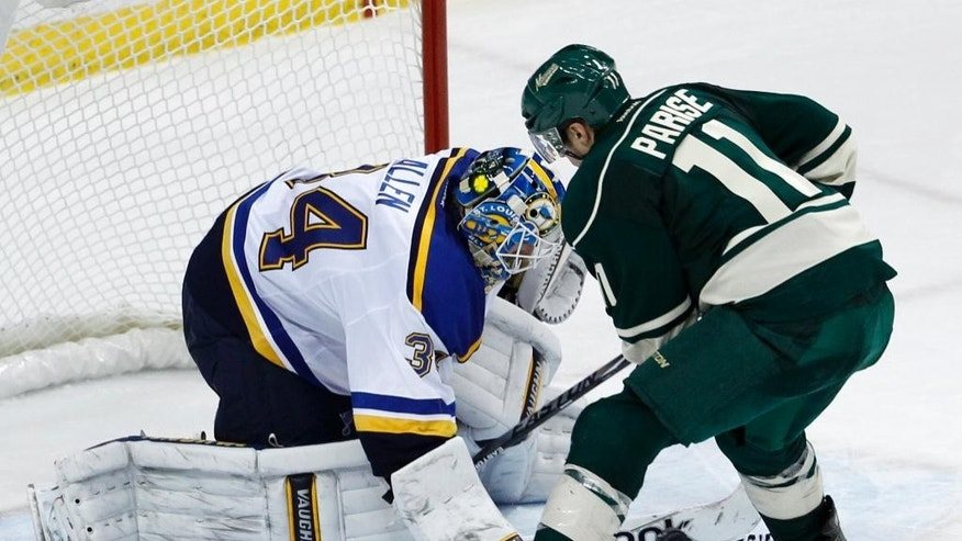 St. Louis Blues goalie Jake Allen (34) deflects a shot by Minnesota Wild left wing Zach Parise (11) during a shootout in an NHL hockey game in St. Paul, Minn., Saturday, Nov. 29, 2014. The Blues won 3-2 in a shootout. (AP Photo/Ann Heisenfelt)