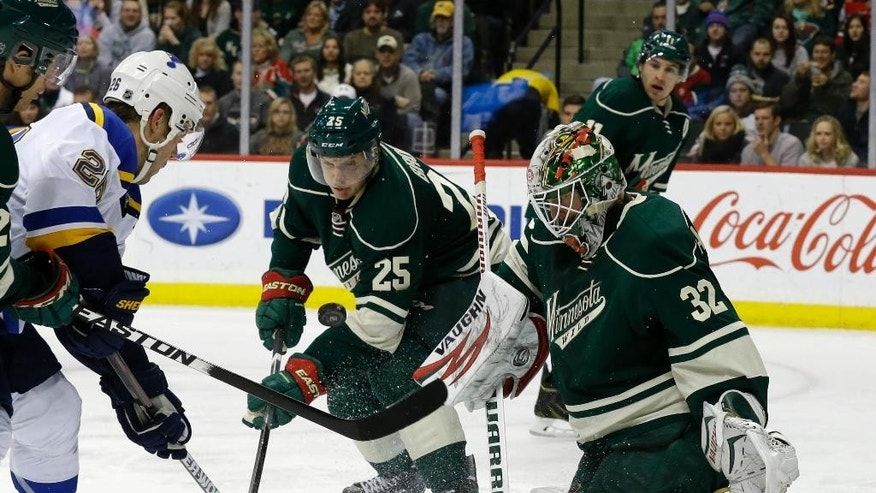 St. Louis Blues defenseman Ian Cole, left, and Minnesota Wild defenseman Jonas Brodin (25) chase a rebound from Wild goalie Niklas Backstrom (32), of Finland, during the second period of an NHL hockey game in St. Paul, Minn., Saturday, Nov. 29, 2014. (AP Photo/Ann Heisenfelt)