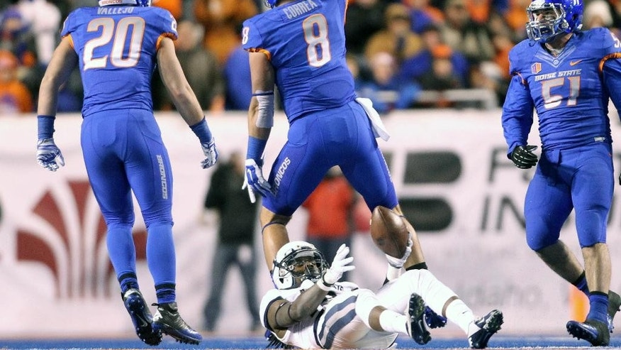 Boise State defensive lineman Kamalei Correa celebrates a tackle of Utah State wide receiver Ronald Butler during an NCAA college football game, Saturday, Nov. 29, 2014 in Boise, Idaho. (AP Photo/The Idaho Statesman, Darin Oswald)  LOCAL TELEVISION OUT (KTVB 7); MANDATORY CREDIT