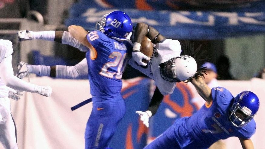Boise State linebacker Tanner Vallejo brings down Utah State wide receiver Ronald Butler after a reception during an NCAA college football game, Saturday, Nov. 29, 2014 in Boise, Idaho. (AP Photo/The Idaho Statesman, Darin Oswald)  LOCAL TELEVISION OUT (KTVB 7); MANDATORY CREDIT
