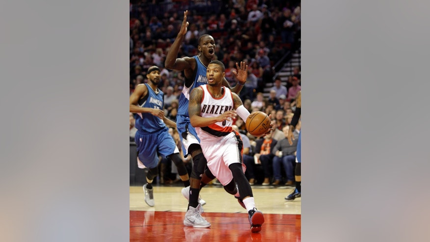 Portland Trail Blazers guard Damian Lillard, right, drives past Minnesota Timberwolves center Gorgui Dieng, from Senegal, during the first half of an NBA basketball game in Portland, Ore., Sunday, Nov. 30, 2014. (AP Photo/Don Ryan)