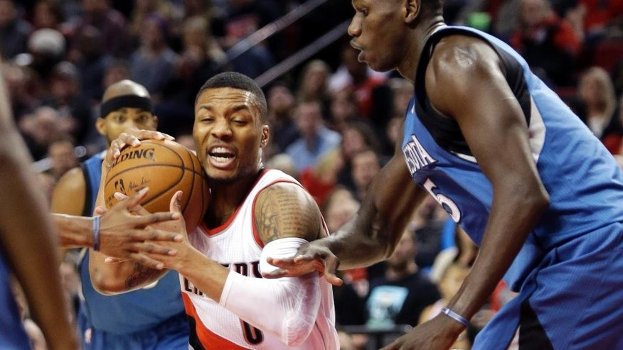 Portland Trail Blazers guard Damian Lillard, left, drives against Minnesota Timberwolves center Gorgui Dieng, from Senegal, during the first half of an NBA basketball game in Portland, Ore., Sunday, Nov. 30, 2014. (AP Photo/Don Ryan)