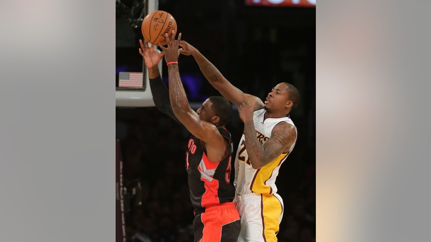 Toronto Raptors' Patrick Patterson, left, goes up for a basket against Los Angeles Lakers' Ed Davis during the first half of an NBA basketball game Sunday, Nov. 30, 2014, in Los Angeles. (AP Photo/Jae C. Hong)