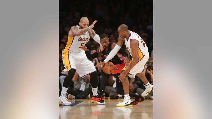 Los Angeles Lakers' Kobe Bryant, right, and Carlos Boozer, left, pressure Toronto Raptors' Terrence Ross during the first half of an NBA basketball game Sunday, Nov. 30, 2014, in Los Angeles. (AP Photo/Jae C. Hong)