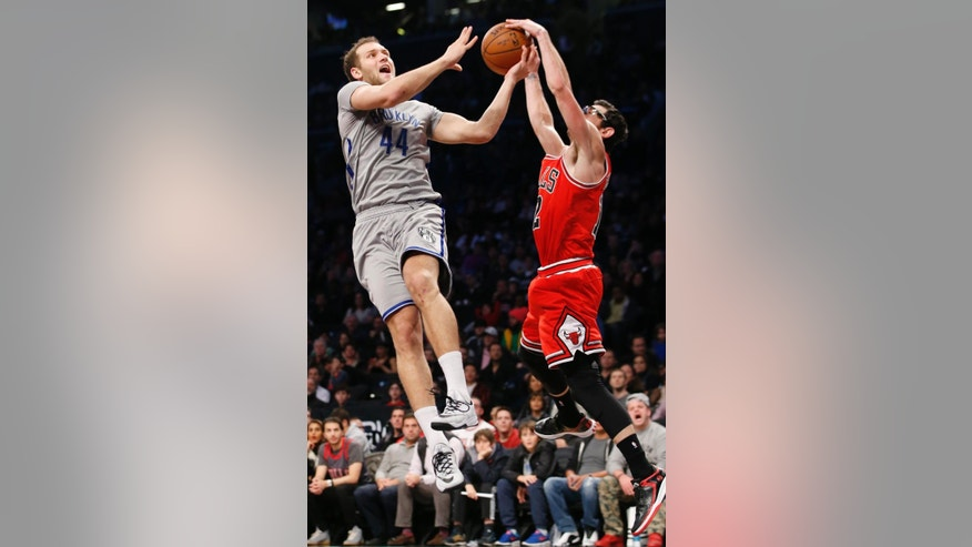 Chicago Bulls guard Kirk Hinrich (12) snatches the ball from Brooklyn Nets guard Bojan Bogdanovic (44) in the second half of an NBA basketball game at the Barclays Center, Sunday, Nov. 30, 2014, in New York. The Bulls defeated the Nets 102-84. (AP Photo/Kathy Willens)