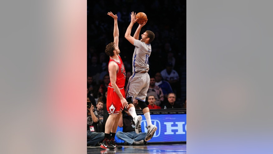 Brooklyn Nets center Brook Lopez (11) shoots over Chicago Bulls forward Pau Gasol in the first half of an NBA basketball game Sunday, Nov. 30, 2014, in New York. (AP Photo/Kathy Willens)