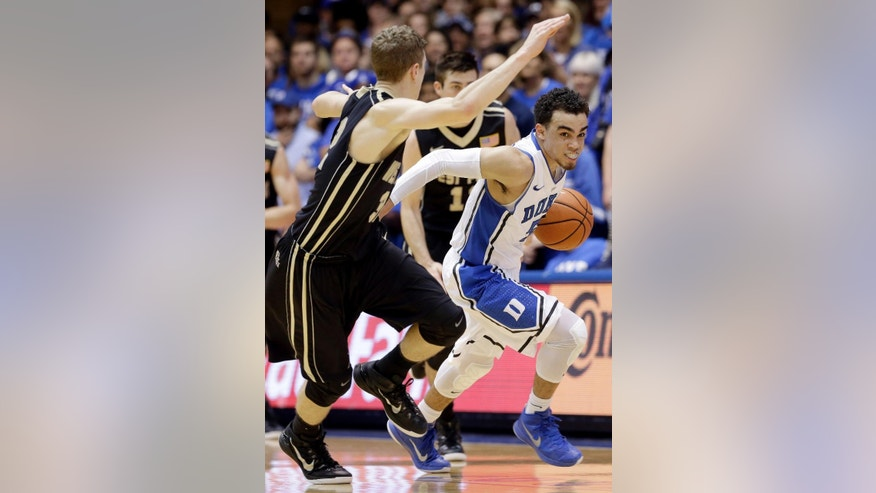 Duke's Tyus Jones, right, dribbles as Army's Tanner Plomb guards during the first half of an NCAA college basketball game in Durham, N.C., Sunday, Nov. 30, 2014. (AP Photo/Gerry Broome)