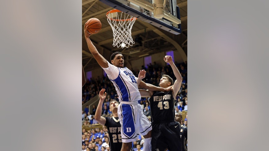Duke's Jahlil Okafor (15) drives to the basket as Army's Luke Morrison (25) and Travis Rollo (43) defend during the first half of an NCAA college basketball game in Durham, N.C., Sunday, Nov. 30, 2014. (AP Photo/Gerry Broome)